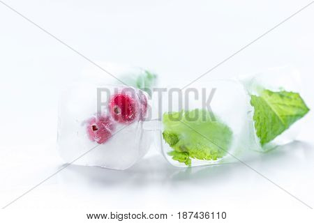 fresh cranberry frozen in ice cubes on white desk background mock-up