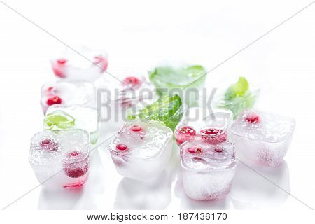 fresh mint and red berries in ice cubes on white desk background