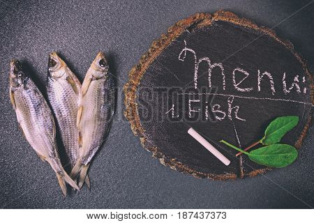 Three dried fish on a black surface next to a wooden stump with an inscription of chalk menus
