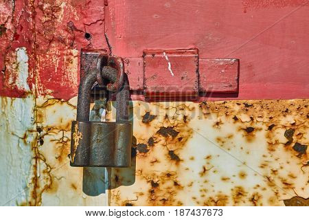 Padlock on an old metal door