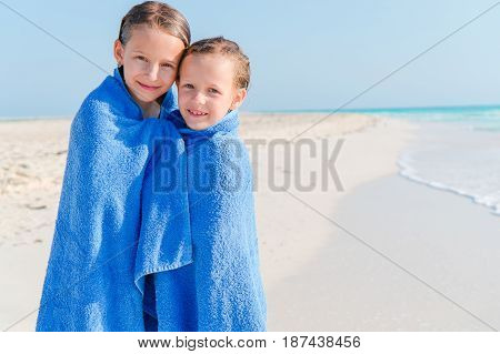 Cute little girls at beach covered with towel