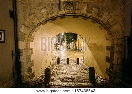 Riga, Latvia. Swedish Gate Gates Is A Famous Landmark. Old Arch Of Swedish Gate In Original State On Troksnu Street In Old Town. Cultural Monument In Lighting At Night Illumination