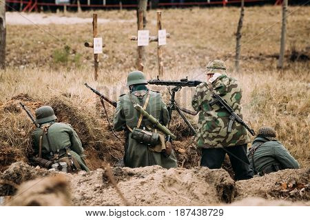 Unidentified Re-enactors Dressed As German Wehrmacht Infantry Soldiers In World War II Hidden Sitting With Rifles And Machine-gun Weapons In An Ambush In Trench In Autumn Field