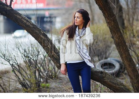 Portrait of a dreamy beautiful woman leaning against a tree in the yard blur closeup