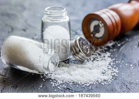 salt in glass bottle scattered on dark kitchen table background