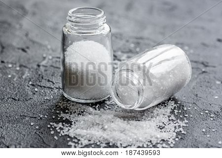 Spices set with salt in glass bottles for cooking on stone kitchen table background