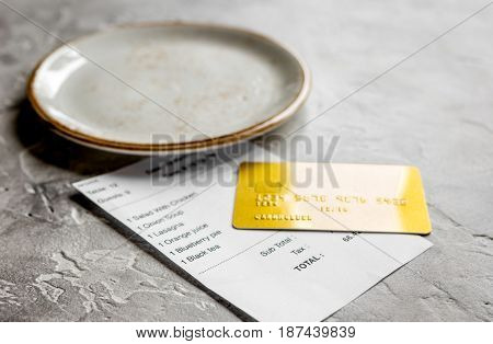 credit card for paying, plate and check on cafe gray stone desk background