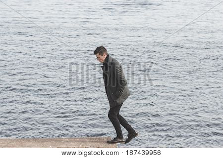 handsome young man in coat walking near water