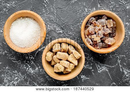 lumps of sugar in bowls on dark kitchen table background top view