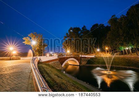Gomel, Homiel, Belarus. Panorama Of Park Channel Flowing Into River Through Stone Bridge In City Park In Evening Or Night Illumination. Lighted Walkways, Greenwood Along Watercourse At Blue Hour