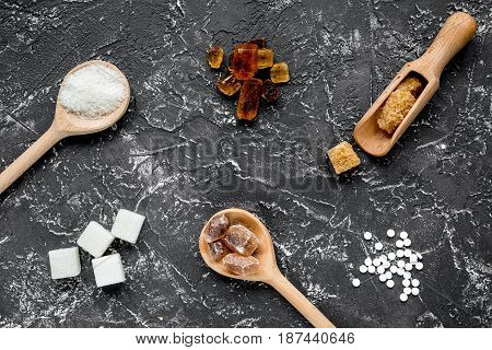 lumps of sugar in spoons on dark kitchen table background top view