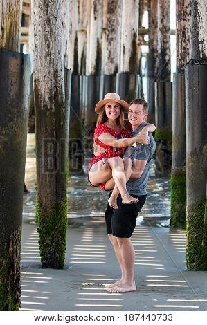 Teenage boyfriend holding girlfriend standing amongst pier pilings.