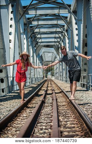 California teen boy and girl balancing on train track rails in front of trestle.