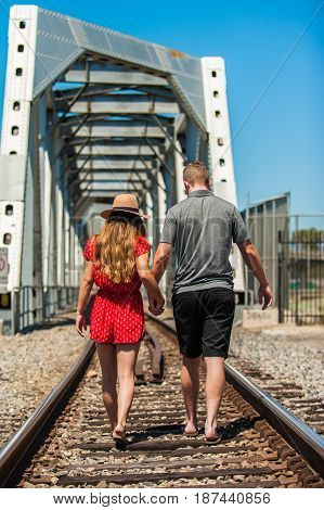 California teen boy and girl walking in middle of train tracks toward trestle.