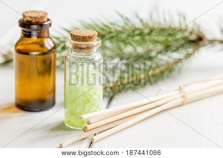 natural fir branches and spruce bath salt and aroma oil on white table background