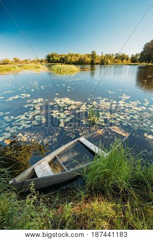 Abandoned Old Wooden Fishing Boat In Summer Lake Or River. Beautiful Summer Sunny Day Or Evening. Forsaken Boat