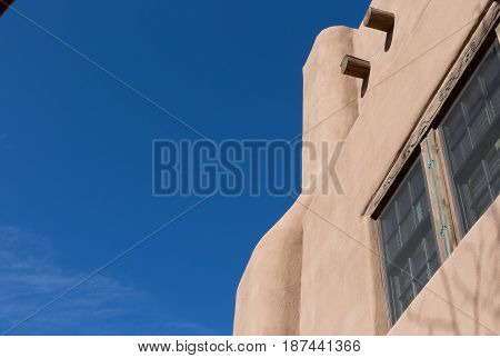 brown adobe house against a blue sky