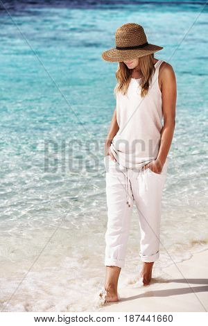 Nice girl walking on the beach, enjoying refreshing clean water, relaxation near the sea, fashion summertime look, enjoying peaceful vacation on the seaside