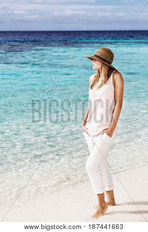 Beautiful woman on the beach, stylish model wearing beige clothes and hat, summer vacation near the sea, Maldives island