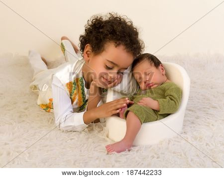 Proud Ethiopian toddler in ethnic costume posing with his newborn brother