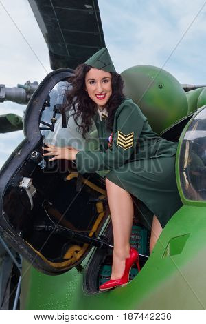 Happy pin-up model in WW2 uniform posing in an old-timer helicopter
