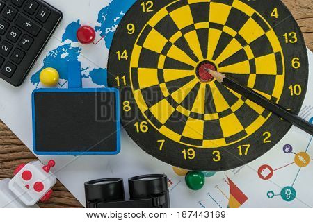 Data analysis SEO concept with pencil dartboard web analytics graph calculator and binoculars on wood table.