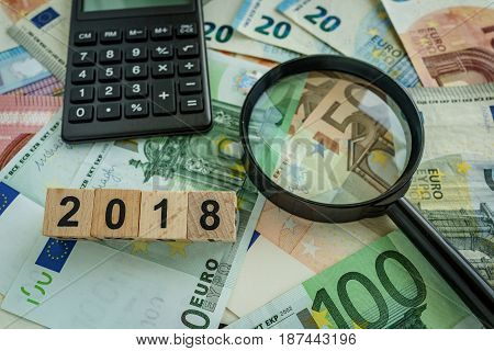 financial tax concept as magnifying glass on pile of euro banknotes calculator and number 2018 on wooden block.