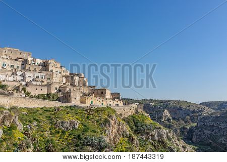 The ancient ghost town of Matera (Sassi di Matera) in beautiful yellow flower in daylight southern Italy.
