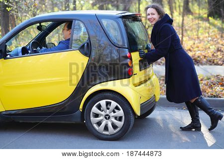 MOSCOW - OCT 25, 2016: Woman pushes Mercedes Smart with man (models with releases) in Sokolniki where conducted Auto Show - Oldtimer, Gallery