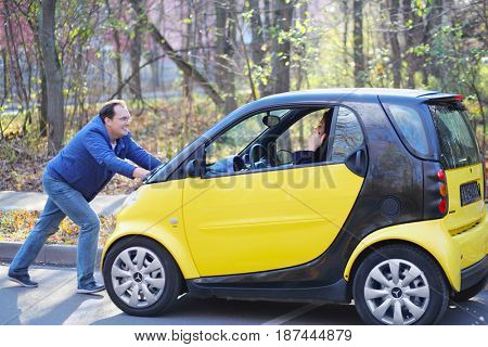 MOSCOW - OCT 25, 2016: Man pushes Mercedes Smart car with woman (models with releases) in Sokolniki where conducted Auto Show - Oldtimer, Gallery