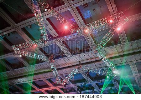 MOSCOW, RUSSIA - NOV 28, 2015: Light devices and beams of color lights at construction in shape of star on ceiling during Disco 80 concert show by Autoradio in Olimpiyskiy sports complex.