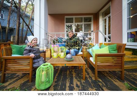 MOSCOW - OCT 25, 2016: Father and daughter (with MR) sit at terrace near house at summer residence of Mosdachtrest company, which manages summer houses fund, services and rents out-of-town property