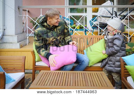 MOSCOW - OCT 25, 2016: Girl (with MR) and father (with MR) play with pillows at terrace in residence of Mosdachtrest company, which manages summer houses fund, services and rents out-of-town property