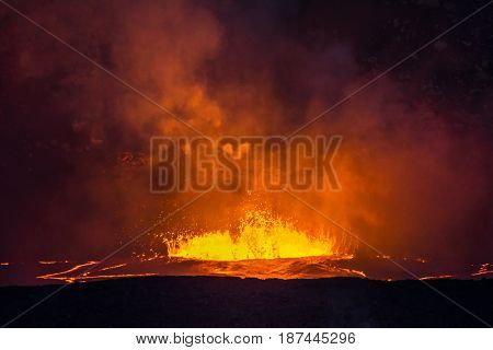 Boiling, erupting lava in the caldera of Kilauea Volcano shoots magma into the air and creates vast amounts of steam from the hot liquid.
