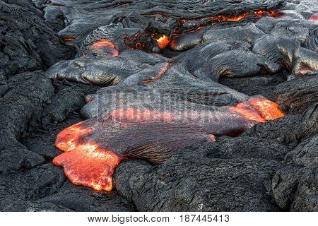 Surface flow lava oozes out of the nooks and crannies of dried lava during an eruption from Kilauea volcano.