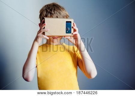 Color shot of a young boy looking through a cardboard, a device with which one can experience virtual reality on a mobile phone.