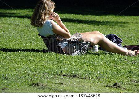 Female beauty talking on cellphone in a public park outdoors.