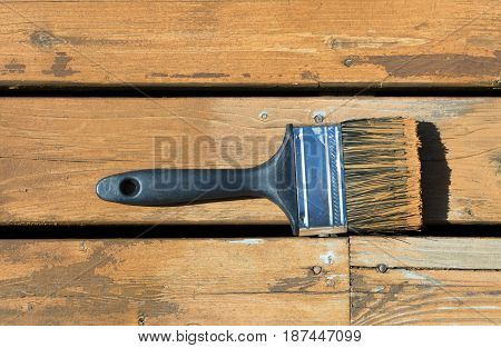 Used paintbrush filled with wood stain on a natural cedar wooden deck