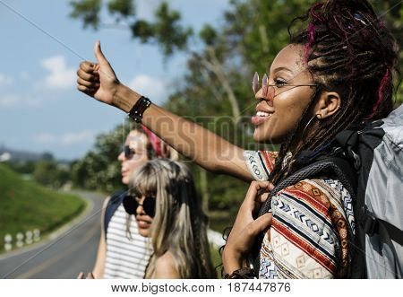 Group of Diverse Backpacker Woman Hitch Hiking on The Street Side
