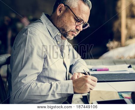 Businessman Working Writing on Paper at Office