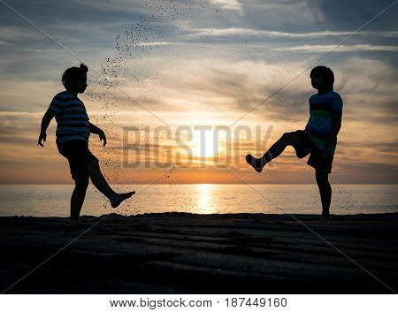 Two happy brothers enjoying beach together at sunset