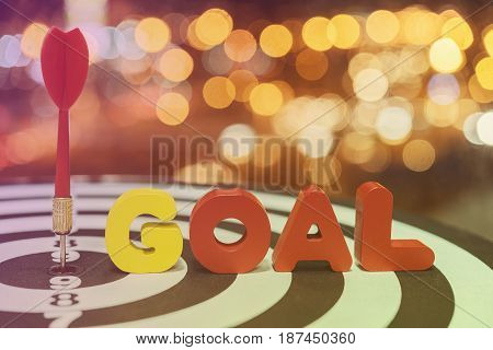 Red dart target arrow hitting on bullseye with goal words over bokeh light background vintage tonemetaphor to accuracy in business success concept