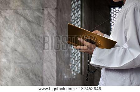 Asian muslim kid reading koran in mosque