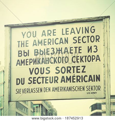 You are leaving the american sector - Historic sign near The Checkpoint Charlie in Berlin, Germany. Retro style
