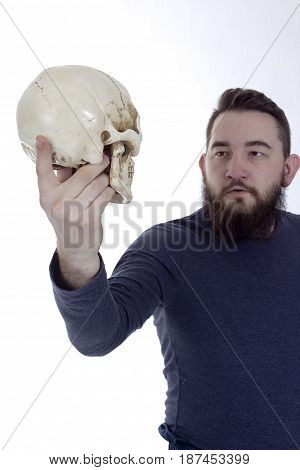 Bearded man with a human skull in his hand