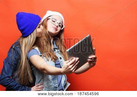 two hipster girls friends taking selfie with digital tablet, studio shot over orange  background