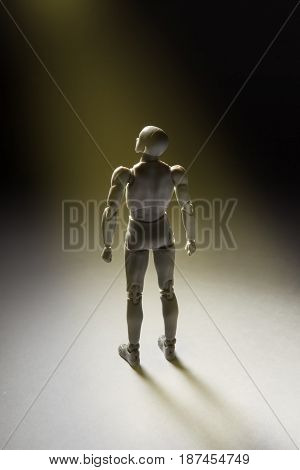 Man Figurine Standing In Powerful Pose Looking Up With Beam Of Light Illuminating It. Vertical Conce