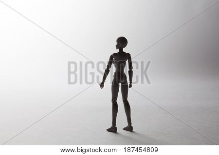 Female Figurine Silhouette Standing Looking To The Left On White Background With Copy Space. Concept