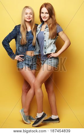 Full body portrait of two happy  hipster girls over yellow background