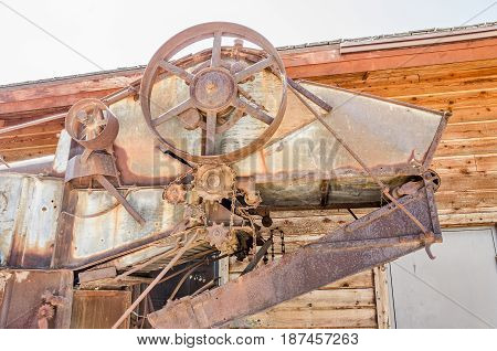 Wheels, gears, and chains on a rusty threshing machine